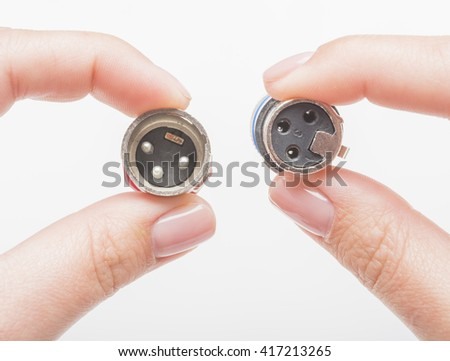 Female hands holding XLR connectors isolated on white