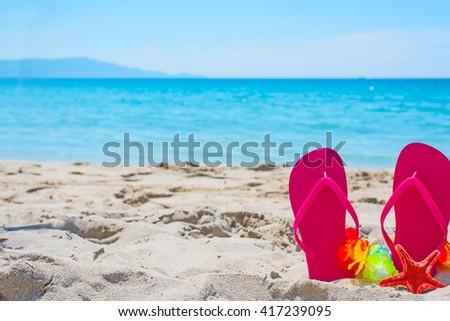 pink flip flops on the sand