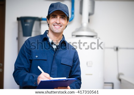 Technician servicing an hot-water heater Royalty-Free Stock Photo #417310561