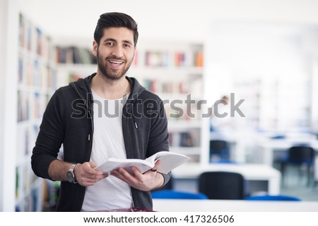 Portrait of happy student while reading book in school library. Study lessons for  exam. Hard worker and persistance concept. #417326506