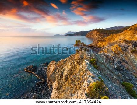Dramatic sunrise on Mediterranean sea. Colorful sprind scene in the small bay near Tekirova village, District of Kemer, Antalya Province. Artistic style post processed photo. #417354424