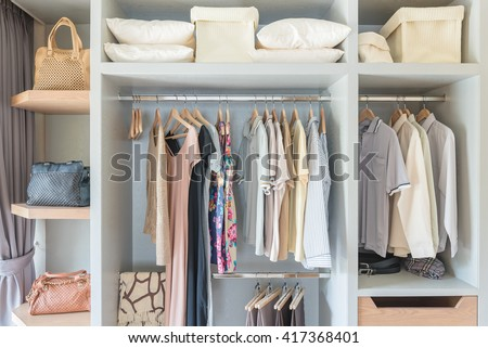 clothes hanging on rail in wooden closet at home #417368401