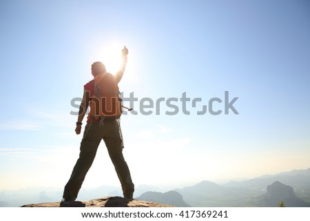 silhouette of young successful woman hiker on mountain peak #417369241