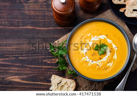 Pumpkin and carrot soup with cream and parsley on dark wooden background Top view Copy space #417471538