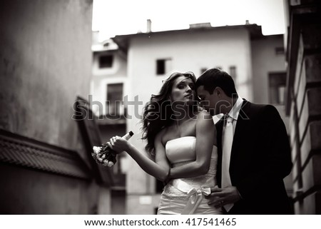 Groom kisses bride's shoulder while she looks in the camera #417541465