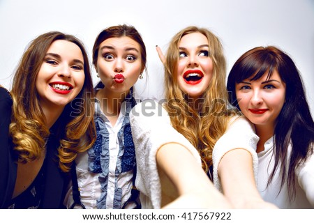 Crazy funny selfie party, four girls having fun at b-day party, stylish black and white clothes. elegant, red lips, funny grimaces, smiling and laughing, making selfie together, toned image with flash