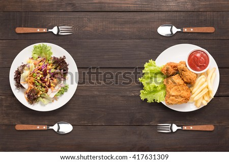 Fresh salad and Fried chicken and french fries on the wooden background. contrasting food. #417631309