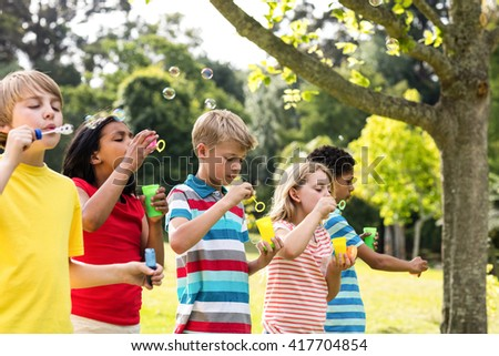 Children running in the park on a sunny day #417704854