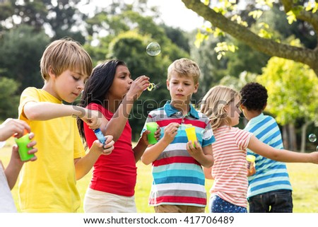 Playful children blowing bubbles wand in the park #417706489