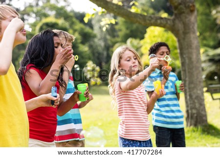 Playful children blowing bubbles wand in the park #417707284
