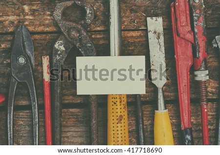 Building and treatment tools set with business card mock up on it on a wooden table, old, vintage building tools.