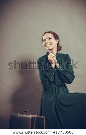 Woman retro style long dark green gown with old suitcase, vintage photo #417730588