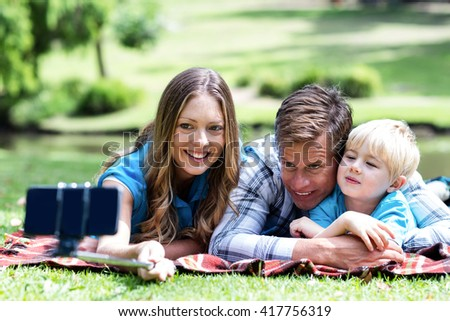 Parents and son taking a selfie on mobile phone with selfie stick in the park #417756319