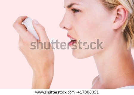 Asthmatic pretty blonde woman using inhaler against beige background #417808351