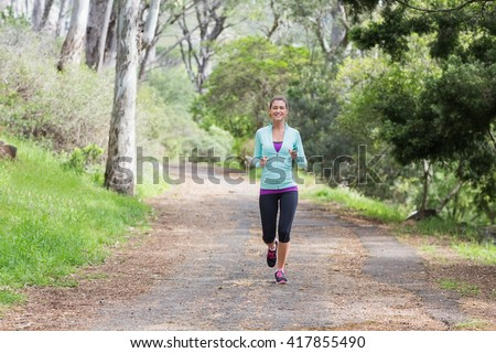 Portrait of young woman jogging on footpath in forest #417855490