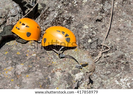 Two helmets on the rock. Climber gear. Two orange  helmets. #417858979