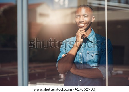 Young African designer looking through window thinking about the future Royalty-Free Stock Photo #417862930