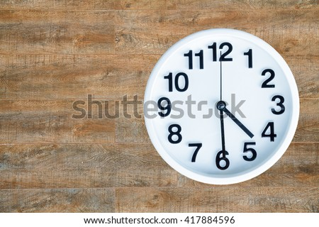 The round white clock shows the time of 4 am or pm and 30 minute. The clock is background is brown wooden with copy space. clipping path in a picture.