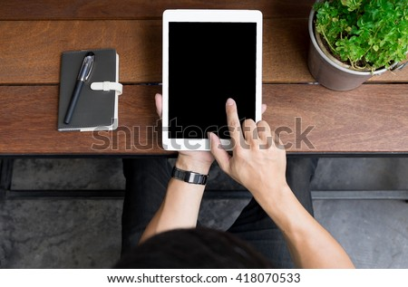 Close up of mans hands using tablet on counter, Image taken from above