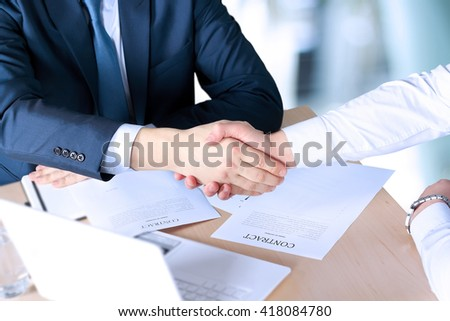 Close-up image of a firm handshake between two colleagues after signing a contract #418084780