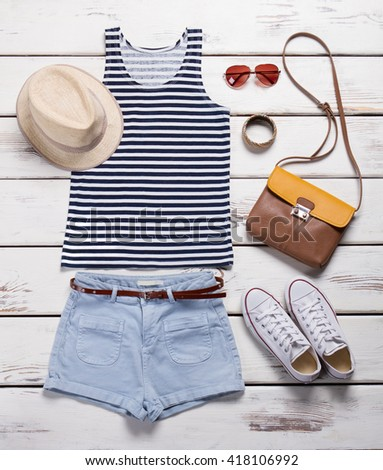 Light shorts with striped top. Girl's summer outfit on showcase. Summer clothing and trendy accessories. Female garments with aviator sunglasses. #418106992