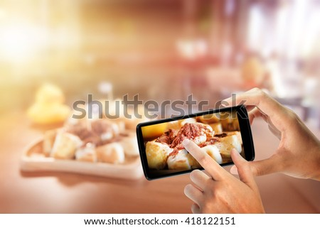 Hand with a smartphone take photo food. enjoy eating.