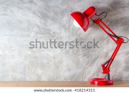 Red lamp on wooden desk in modern room, with copy space. #418214311