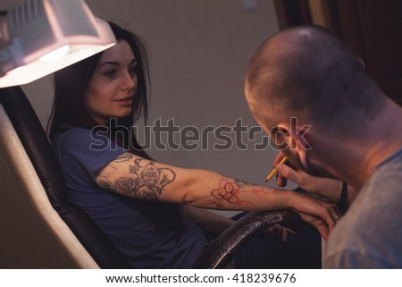 Tattooer is making scetch for future tattoo on the woman's hand #418239676