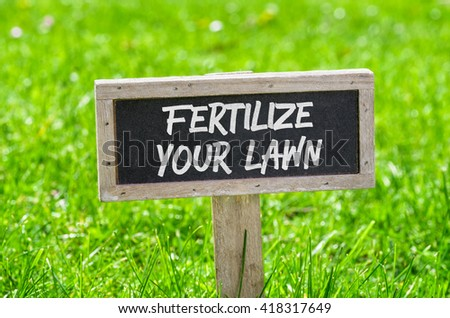 Sign on a green lawn - Fertilize your lawn #418317649