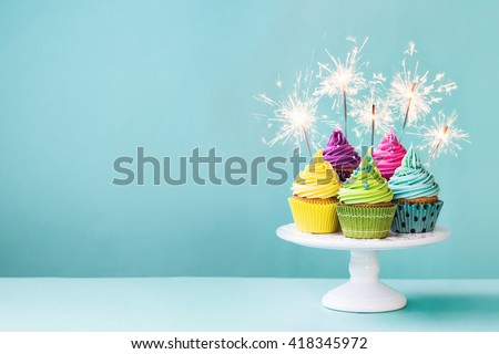 Cupcakes on a cake stand with sparklers Royalty-Free Stock Photo #418345972