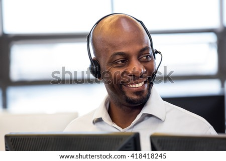 Man working on computer with headset in office #418418245