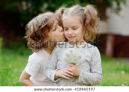 Beautiful little girl collects dandelions in the yard and boy kiss her.