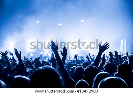 silhouettes of concert crowd in front of bright stage lights Royalty-Free Stock Photo #418492903