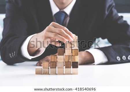 Closeup of businessman making a pyramid with empty wooden cubes Royalty-Free Stock Photo #418540696