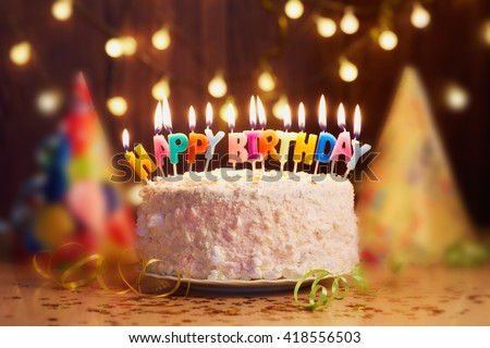 Birthday cake with candles, bright lights bokeh. Royalty-Free Stock Photo #418556503