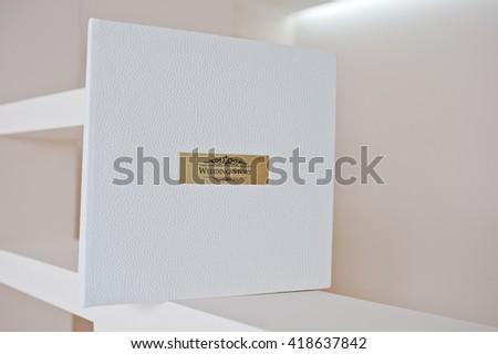 White leather wedding album with golden metallic insert text Wedding Story #418637842