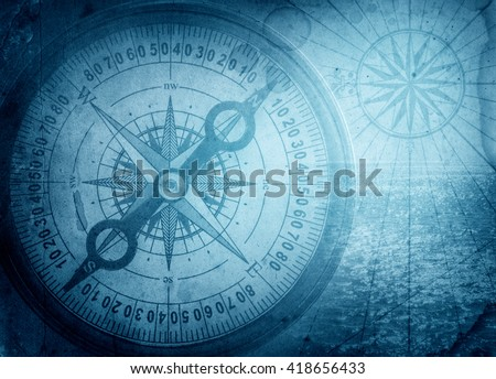 Old compass on vintage map. Pirate and nautical theme grunge background. Royalty-Free Stock Photo #418656433