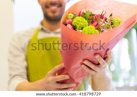 people, shopping, sale, floristry and consumerism concept - close up of happy florist man holding bunch wrapped in paper at flower shop #418798729