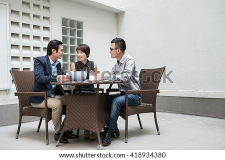 Vietnamese business team having meeting in outdoor cafe #418934380