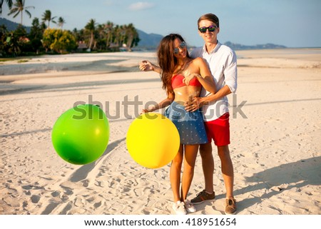 Lovely Portrait of two happy young people dating and having fun on the beach.handsome man make surprise for his Girl,holding her man and  keeping color balloons in hand.Summer beach background.Outdoor #418951654