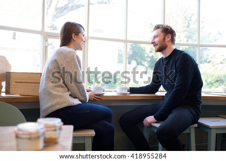 Young Couple Sitting At Table In Coffee Shop Together #418955284
