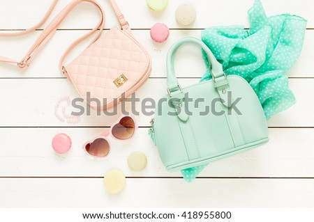 Pastel theme mood board with fashion accessories (bags, sunglasses, scarf) for girls. White rustic wooden background. Flat lay composition (from above, top view).