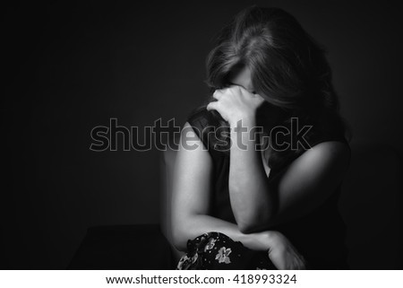 Black and white portrait of a crying sad and depressed woman with a dark background #418993324