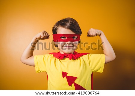 Boy dressed as a superhero on yellow background #419000764