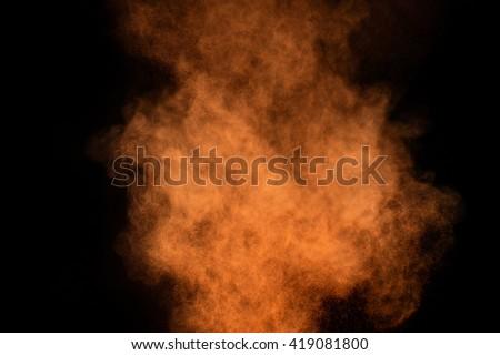 Orange powder explosion on black background. Colored powder cloud. Colorful dust explode. Paint Holi. #419081800