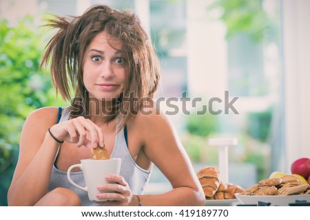 Young messy woman have breakfast in the kitchen Royalty-Free Stock Photo #419189770