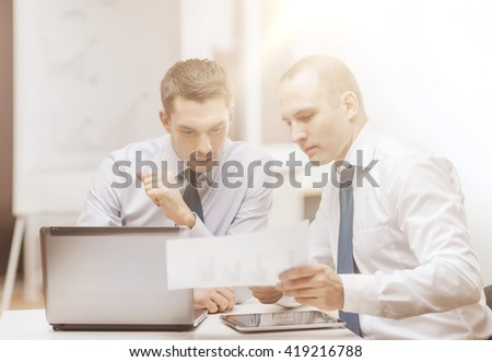 business, technology and office concept - two businessmen with laptop, tablet pc computer and papers having discussion in office #419216788