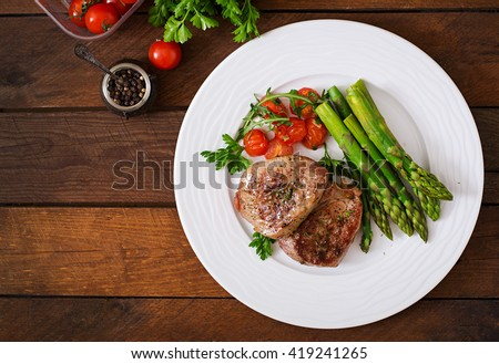 Barbecue grilled beef steak meat with asparagus and tomatoes. Top view #419241265