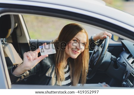 Attractive young brunette woman proudly showing her drivers license #419352997
