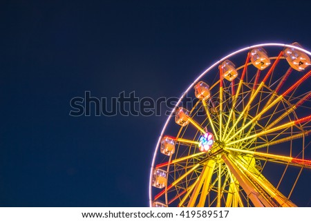 Part of ferris wheel against a blue sky background with lights neby night lighting Royalty-Free Stock Photo #419589517